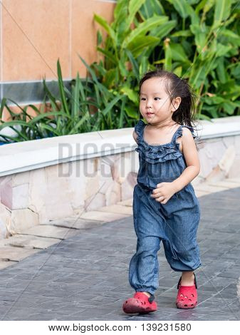 Little Asian cute baby girl running on the path