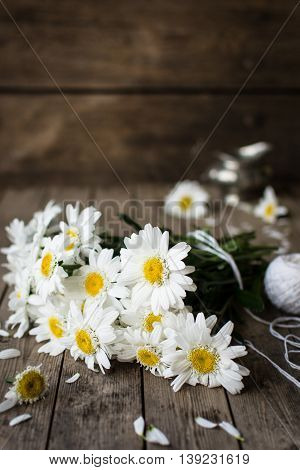 A bouquet of daisies, laying on a wooden board