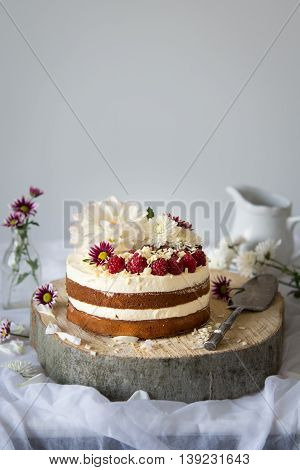 White cake with white chocolate frosting and raspberries
