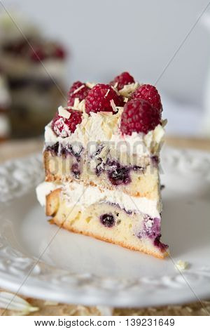 Piece of white cake with white chocolate frosting and berries