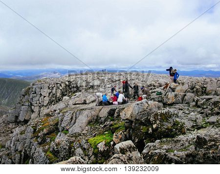 FORT WILLIAM UNITED KINGDOM - JULY 22 2011: Tourists resting and enjoying the view on top of Ben Nevis in Scotland the highest mountain in the United Kingdom.