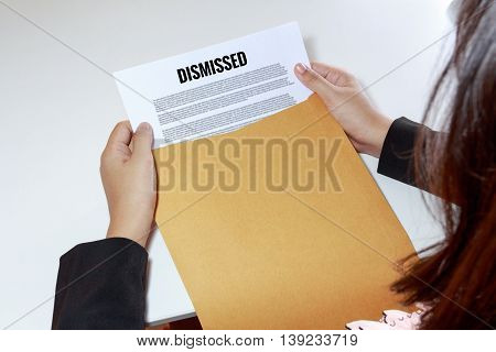 Businesswoman hands holding the dismissed document in envelope.