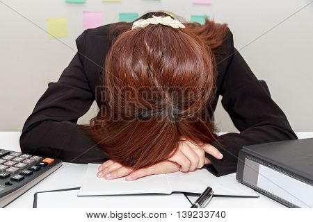 Stressed businesswoman bend down the head or sleep at her desk overwork concept