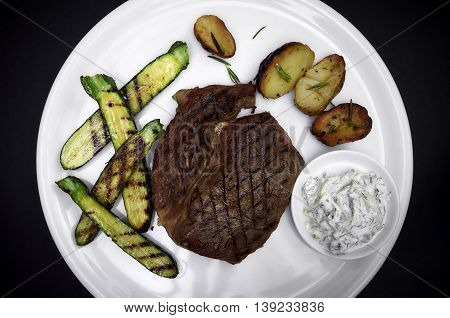Juicy barbecue steak with potatoes, courgettes and tartar souce