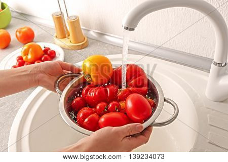 Female hands washing tomatoes in colander at kitchen