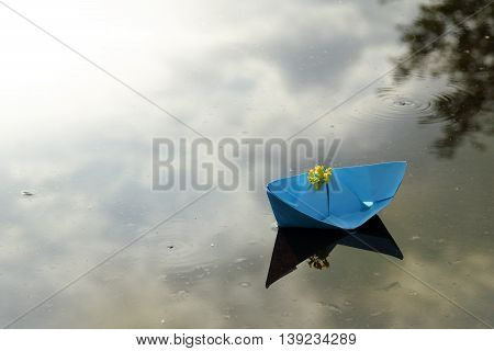 ship from the blue paper and yellow flowers floating in water