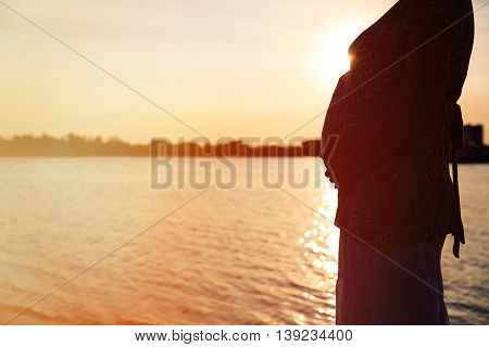 silhouette of pregnant woman at sunset sky