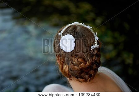 Hairstyle in a boho style with handmade lace. Closeup on the background of water