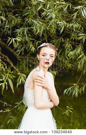 Girl in a beautiful white lace dress boho style looking at the camera. Arms crossed over his chest