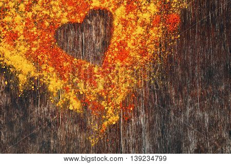 Turmeric and paprika powder with heart silhouette on wooden background