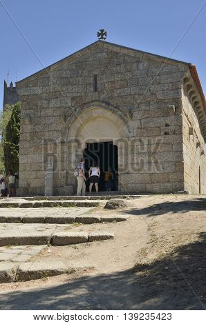 GUIMARAES, PORTUGAL - AUGUST 9, 2016: People going into the Church of Saint Miguel do Castelo a romanesque church constructed within the circle of the Castle of Guimaraes Portugal.