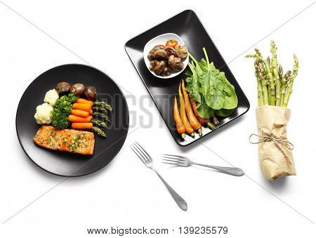 Tasty dish with baby carrots and salmon on black plate, top view