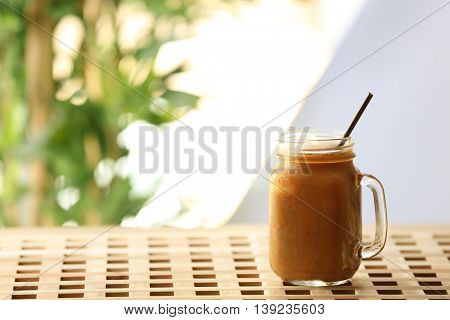 Iced coffee in glass jar on wooden table