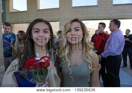 JOLIET, ILLINOIS / UNITED STATES - MAY 19, 2015: A girl proudly holds her diploma, and a bouquet of red roses, after an eighth grade graduation ceremony held at Plainfield South High School.