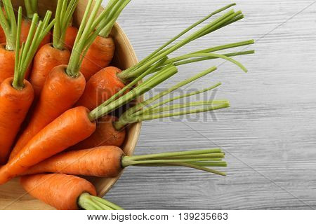Fresh carrots in a bowl on wooden background