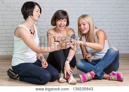 One young woman showing her smartphone girlfriends, who are very surprised