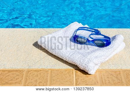 Swimming goggles and bath towel near blue swimming pool