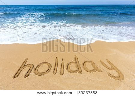 Word holiday written at coast in sandy beach