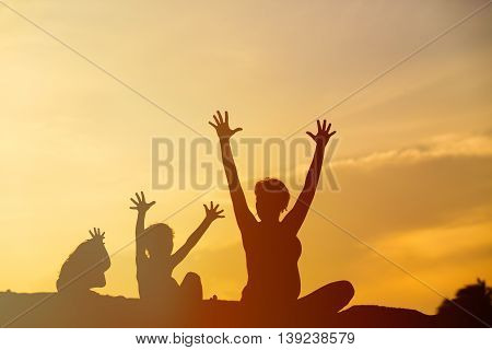 Silhouette of happy mother and kids at sunset sky