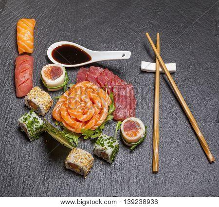 Sashimi and sushi rolls served on stone slate