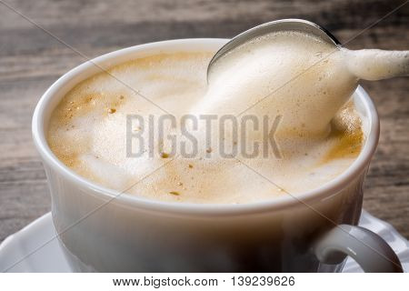 Cappuccino with milk foam and spoon close-up.