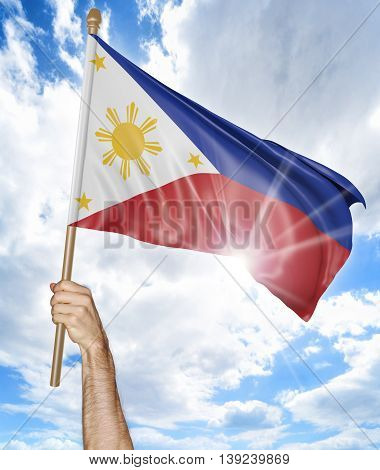 Person's hand holding the Philippines national flag and waving it in the sky, 3D rendering