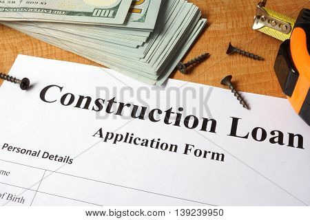 Construction loan form on a wooden table.