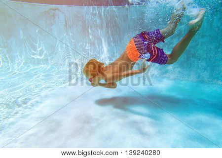 little boy swimming diving underwater at pool