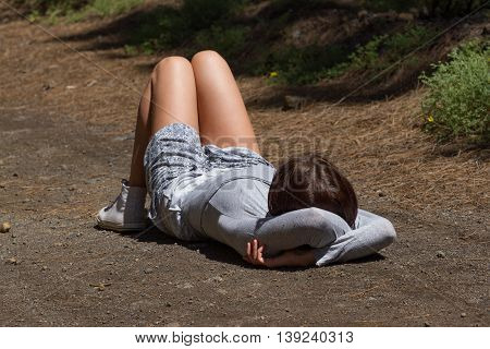 Young girl make activity in forest before activity. Leisure summer time. Lying