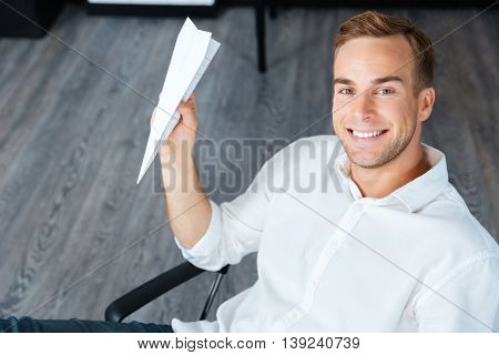 Happy handsome young businessman sitting and throwing paper plane in office