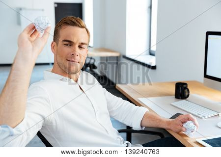 Handsome young businessman crumpling and throwing paper in office