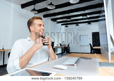 Happy attractive young businessman sitting and drinking coffee at workplace