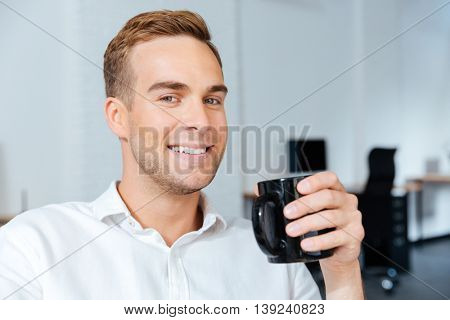 Portrait of happy handsome young businessman drinking coffee in office