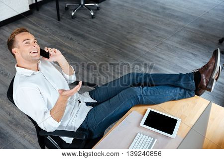 Top view of smiling confident young businessman sitting and talking on mobile phone at workplace