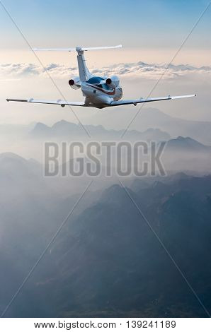 perspective view of jet airliner in flight with mountains background.