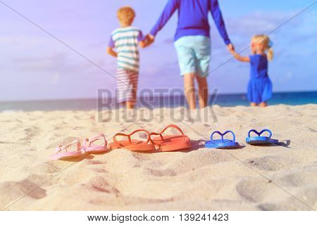 father with son and daughter walking at beach, flip flops on sand