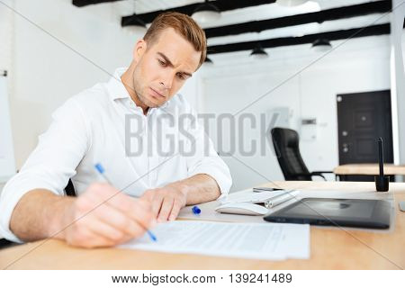 Serious young businessman sitting in office and writing