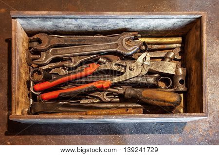 Wooden tool box of hand tools with old and dirty rusty wrenches ring spanners pliers screwdrivers chisel and other do-it-yourself (DIY) tools.