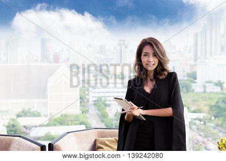 Successful worker. Smiling business woman holding a tablet and pen in his hands while businessman in formal attire is standing in front of office windows.