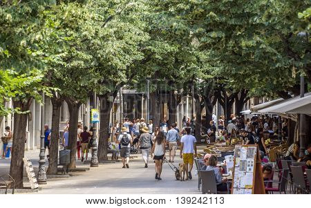 GIRONA SPAIN - JULY 6 2016: Hundreds of people promenading in the busiest street of Girona the Ramblas.