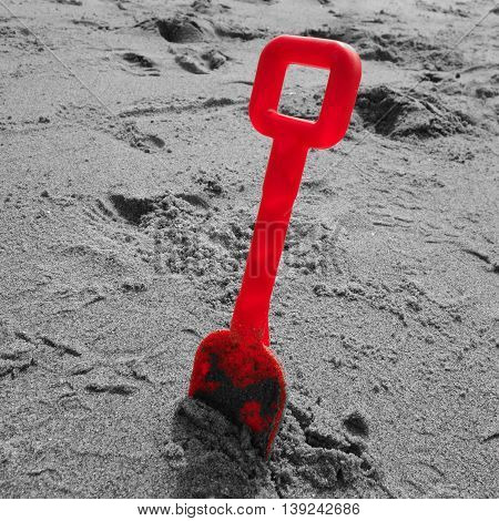 Red plastic toy spade stuck in sand on a beach