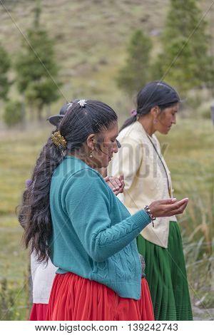CUENCA, ECUADOR, OCTOBER - 2015 - Group of native ecuadorian catholic indigenous women praying at outdoors in Cuenca outskirts Ecuador South America