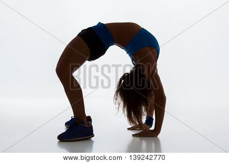 Sport and active lifestyle. Sporty flexible girl fitness woman in sportswear doing stretching exercise on light background. silhouette