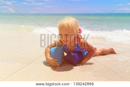 happy little girl play with armbands at sea, swimming safety