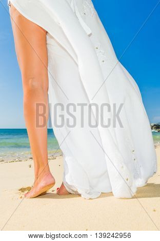 girl is walking on the sand with a flowing white sarong