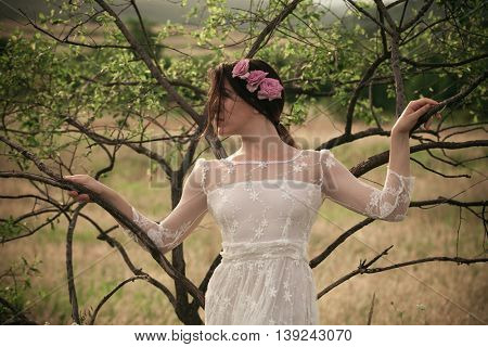 young woman in  white lacy dress and roses in hair lean on tree branch summer day