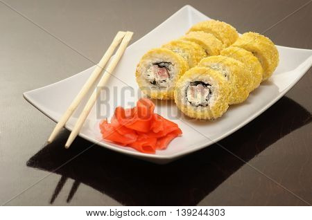 yellow chicken sushi roll on the plat with ginger and chopsticks