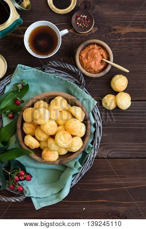 Savory double cheese puffs in a wooden bowl