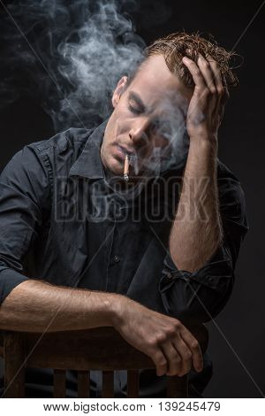 Stylish guy in dark shirt sits on a chair on the black background in the studio. He smokes a cigarette with closed eyes. Left hand is on the head, right hand is on the chair. Vertical low-key photo.