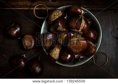 Whole raw chestnuts in a metal bowl